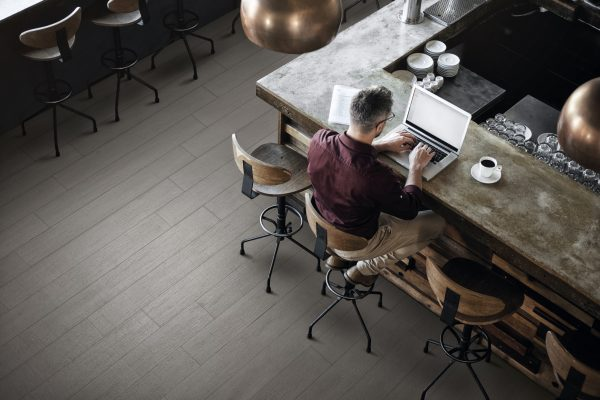 High angle shot of a businessman working on his laptop at the bar in a cafe